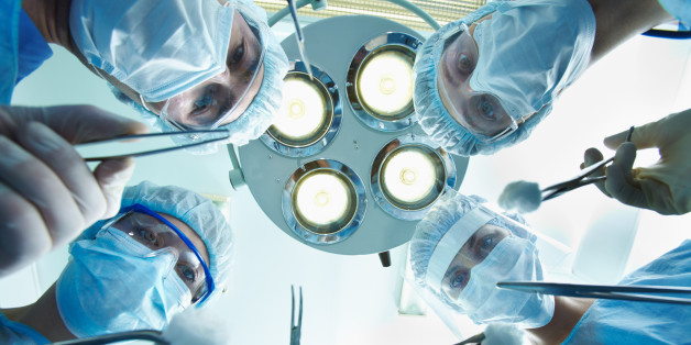 Low angle view of four surgeons bending over the patient during operation
